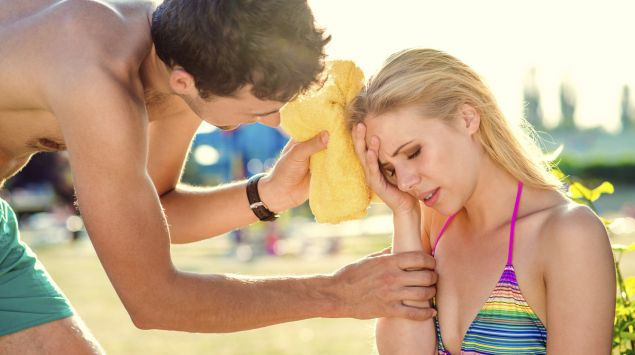 Man siehte eine Frau am Strand, die sich erschöpft an den Kopf fasst. Ein Mann kümmert sich um sie.