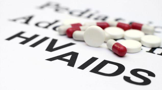 Die Worte HIV und AIDS, daneben verschiedene Tabletten.