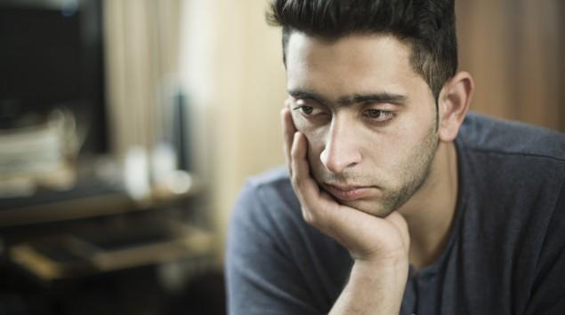 Ein junger Mann guckt traurig und stützt das Kinn auf die Hand.
