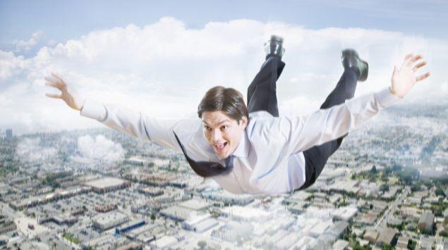 Ein Geschäftsmann fliegt über einer Stadt.