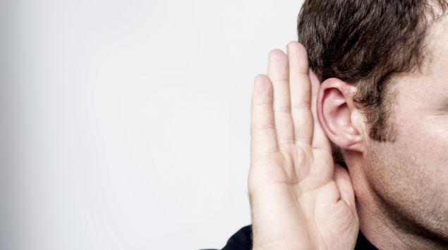 Das Bild zeigt einen Mann, der seine Hand hinter das Ohr hält.