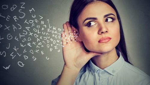 Man siehte eine Frau mit Hand am Ohr und Buchstaben, die auf das Ohr zufliegen.