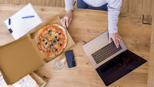 Eine Person sitzt mit Laptop und Pizza am Schreibtisch.