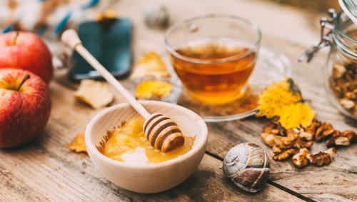 Eine Tasse Tee und ein Schälchen Honig stehen in herbstlicher Umgebung