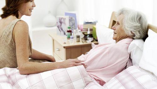 Das Bild zeigt eine ältere Frau, die im Bett liegt und einen jüngere Frau, die auf der Bettkante sitzt.