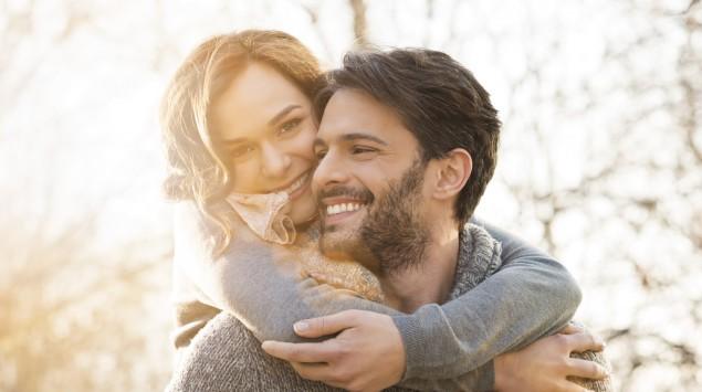 Zu sehen ist ein fröhliches Paar; der Mann trägt die Frau huckepack.