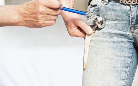 Arthrose: Ein Mann hält sich eine Hüftgelenksprothese an die Hüfte.