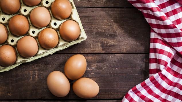 Auf einem Tisch liegen neben einem vollen Eierkarton ein paar einzelne Eier und ein kariertes Küchentuch.