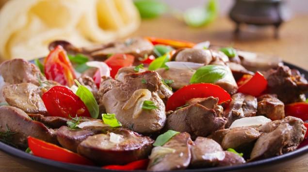 Man sieht einen Teller mit Hühnerleber, Tomaten, Zwiebeln und Basilikum.