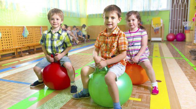 Drei Kinder auf Hüpfbällen in einer Turnhalle.