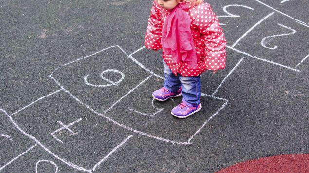Ein kleines Mädchen im Hüpfkästchenspiel.