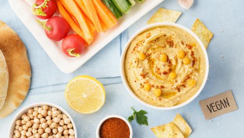 Auf einem Tisch stehen eine Schale Hummus und teils zu Stäbchen geschnittenes Gemüse.