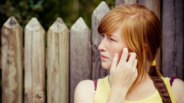 Ein Mädchen kratzt sich im Gesicht.