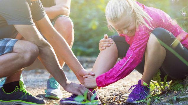 Das Bild zeigt eine verletzte Joggerin, die am Boden sitzt und ihr Sprunggelenk hält.