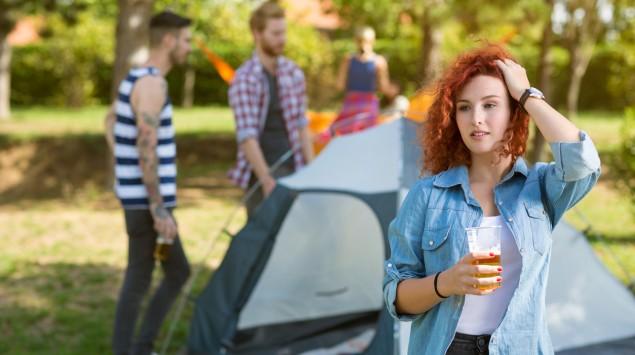 Eine Jugendliche vor einem Zelt, in der Hand einen Becher Bier.