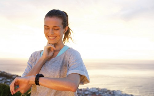 Das Bild zeigt eine junge Sportlerin, die ihren Puls misst.