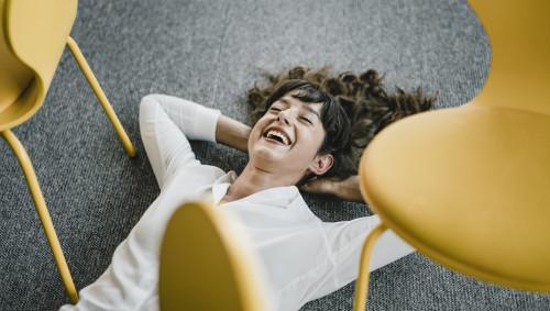 Eine lachende Frau liegt auf dem Boden zwischen Bürostühlen.