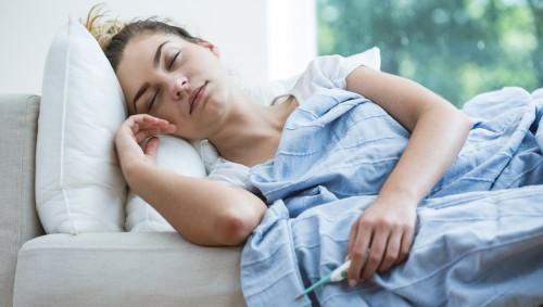 Eine krank und erschöpft wirkende Frau liegt zugedeckt auf einem Sofa und hält ein Fieberthermometer in der Hand.