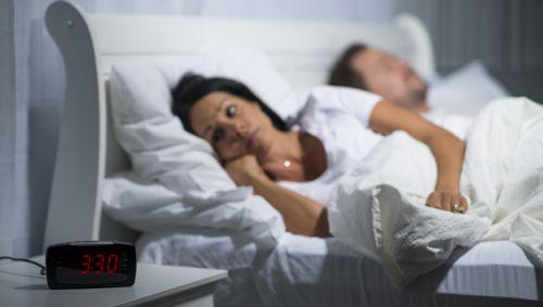 Eine Frau liegt neben einem schlafenden Mann wach im Bett; ihr Wecker zeigt 3:30 Uhr an.