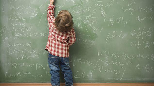 Ein kleines Kind schreibt Formeln an eine Tafel.