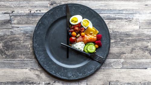 Ein Teller mit Besteck als Uhr mit Essen drauf