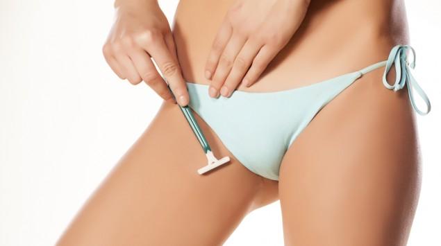 Eine Frau im Slip rasiert sich am Intimbereich.