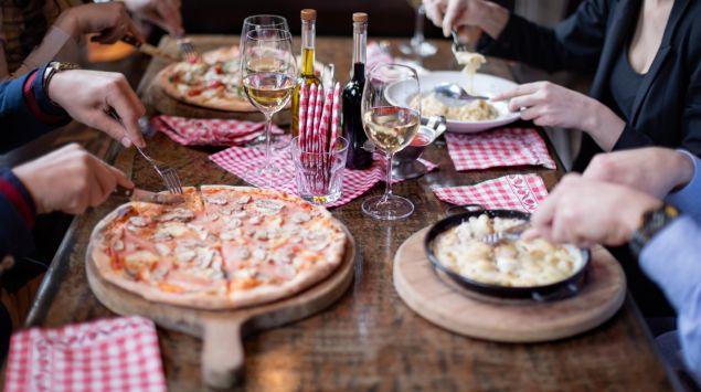 Man sieht einen Tisch in einem italienischen Restaurant, auf dem Pizza- und Pasta-Gerichte stehen.