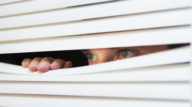 Eine Person schaut durch eine Jalousie.