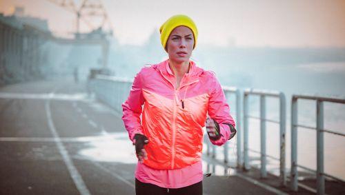 Eine Frau mit einer gelben Mütze joggt über eine Straße.