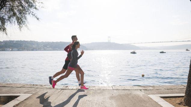 Das Bild zeigt zwei Personen, die am Fluss entlang joggen.