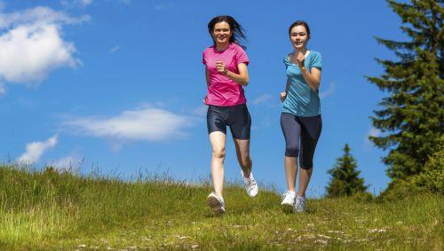 Man sieht zwei junge Frauen, die über eine Wiese joggen.