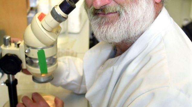John Sulston sitzt in einem Labor vor einem Mikroskop.