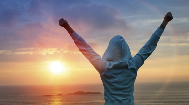Eine junge Frau in Kapuzenjacke blickt in Richtung Sonne, die gerade im Meer untergeht, und reckt die Arme in die Luft.