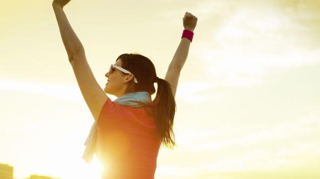 Man sieht eine Frau mit Sonnenbrille und Handtuch, die im Morgengrauen jubelnd die Arme in die Luft streckt.