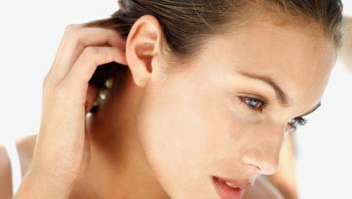 Man sieht eine Frau, die sich hinter dem Ohr kratzt.