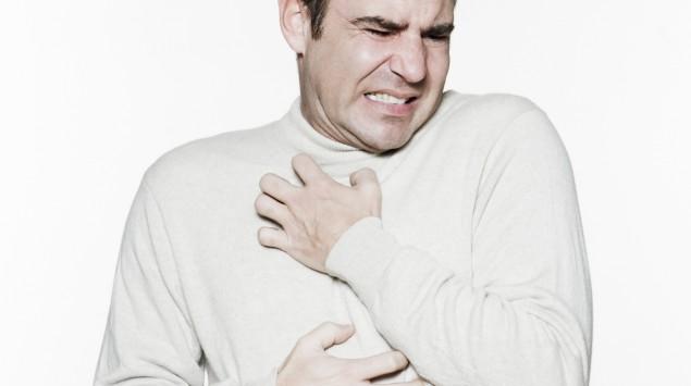 Das Bild zeigt einen Mann, der sich am Brustkorb kratzt.