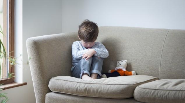 Ein Junge sitzt zusammengekauert auf dem Sofa.