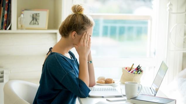 Eine junge Frau am Schreibtisch wirkt erschöpft.
