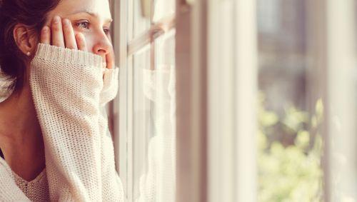 Eine junge Frau schaut nachdenklich aus dem Fenster.
