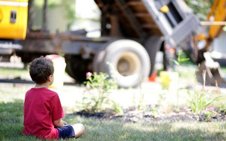 Ein in sich gekehrter Junge sitzt auf einem Stuhl und schaut zu Boden.