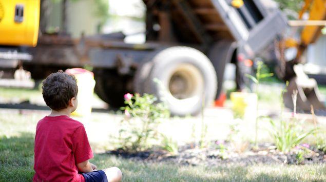 Ein Junge sitzt auf einer Wiese und betrachtet einen Bagger.