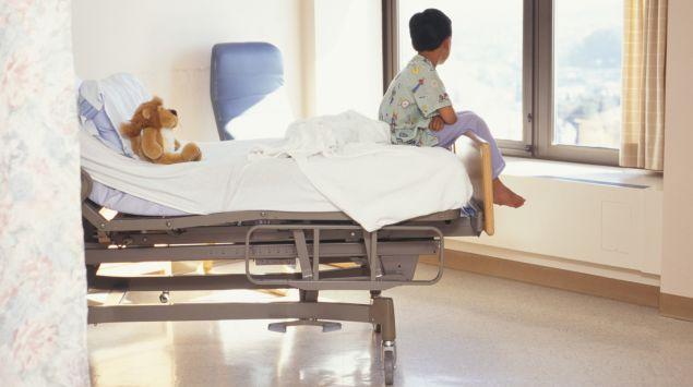 Das Bild zeigt einen Jungen, der allein auf einem Krankenhausbett sitzt.