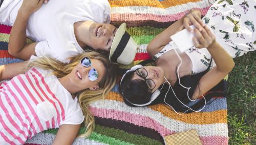 Junnge Leute liegen zusammen auf einer Decke im Park