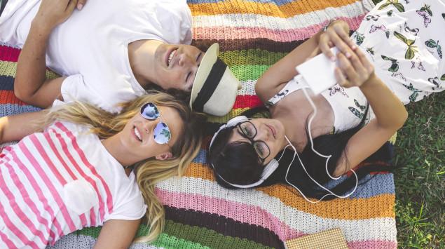 Junge Leute liegen im Park auf einer Decke: Sie fühlen sich sicher vor Covid-19, dabei kann das Coronavirus jeden treffen