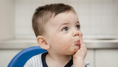Ein kleiner Junge hält sich die Hand vor den Mund.