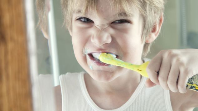 Ein Junge putzt sich die Zähne.