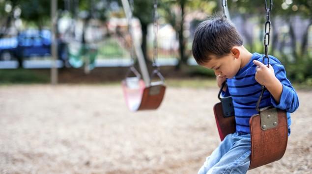 Ein introvertierter Junge auf einer Schaukel