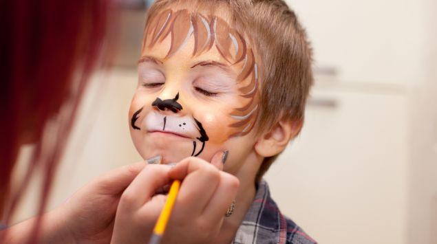 Ein kleiner Junge wird geschminkt.