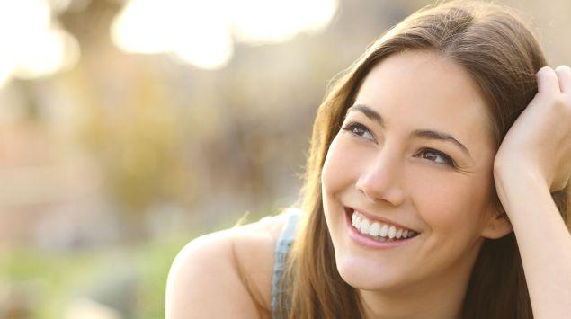 Das Bild zeigt eine junge Frau, die lächelnd in die Ferne guckt.