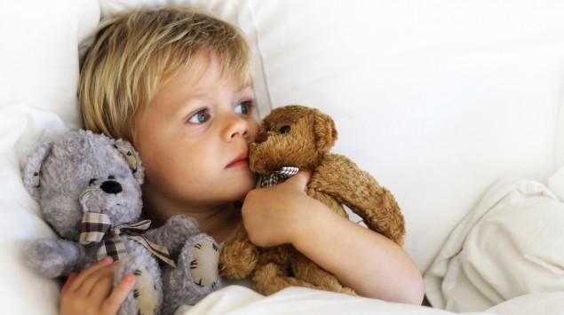 Ein kleiner Junge liegt im Bett und hält in jedem Arm einen Teddybären.